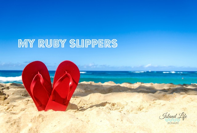 Red flip flops in heart shapes on the sandy beach Bonaire.