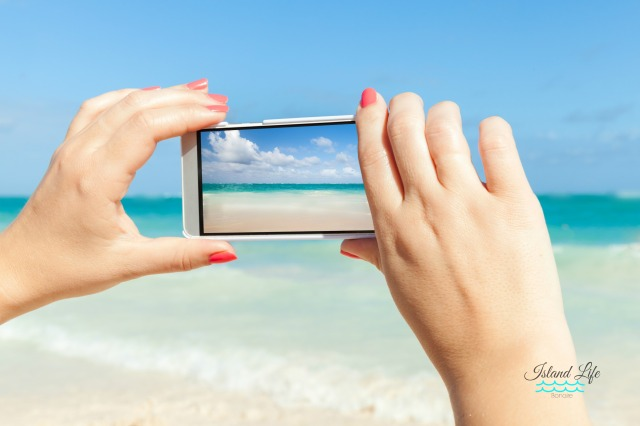Woman using cell phone for taking sea landscape photo on a beach.